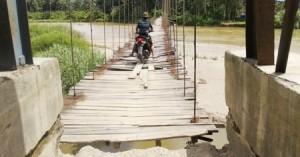salah satu seorang warga melintas di jembatan yang buruk di kampung baru.madina