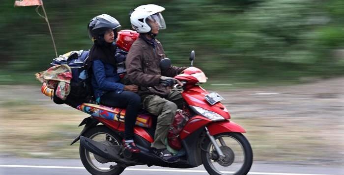 Pemudik menggunakan sepeda motor melintas di Jl. Wates, Yogyakarta, Jumat (25/7). Meskipun harus menempuh perjalanan jauh dengan sepeda motor, namun hal tersebut tidak menyurutkan niat para perantau untuk pulang merayakan lebaran di kampung halaman bersama keluarga. ANTARA FOTO/Noveradika/ss/nz/14