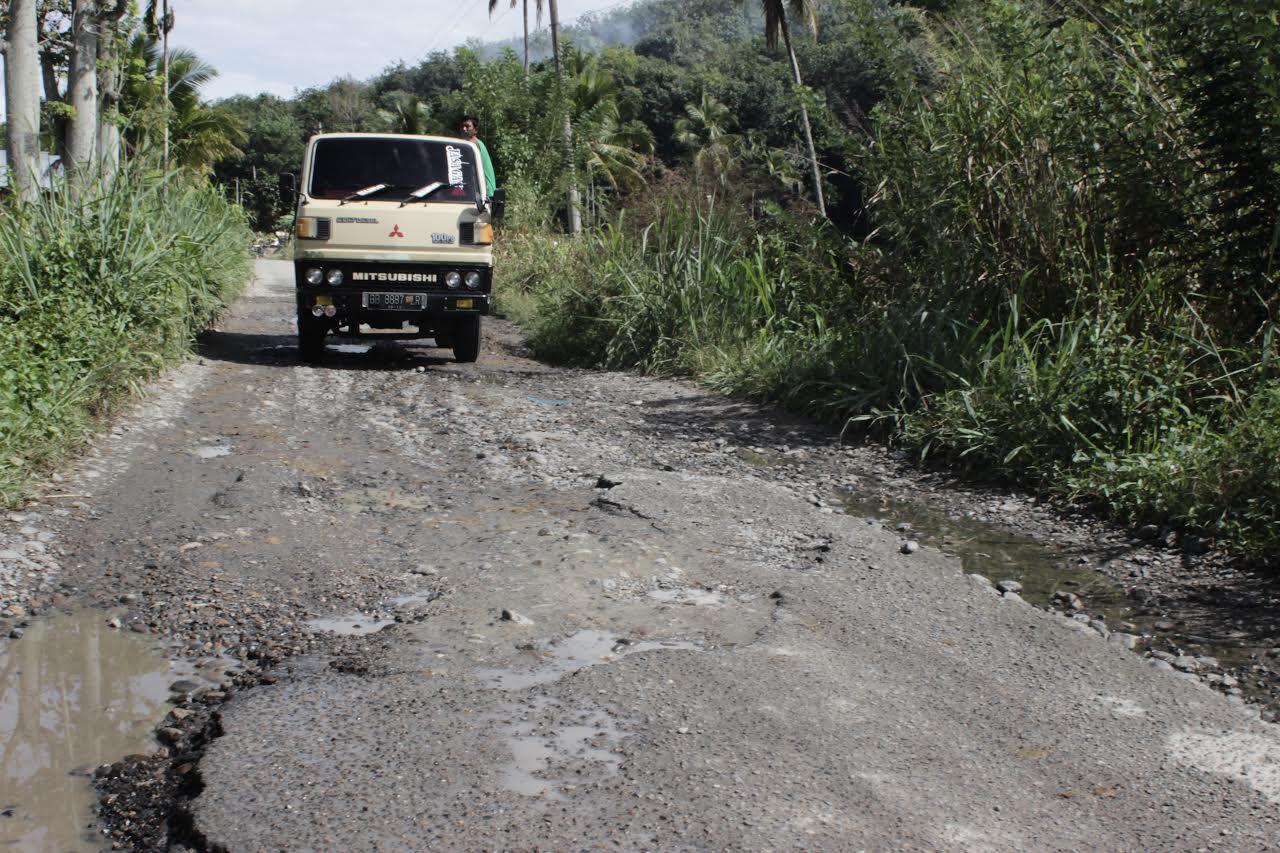 Keterangan Foto : Sebuah mobil ketika melewati jalan yang rusak di titik Saba Salambue Desa Salambue Kecamatan Panyabungan
