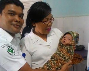 Petugas Rumah Sakit sedang menggendong dan akan memandikan bayi tersebut