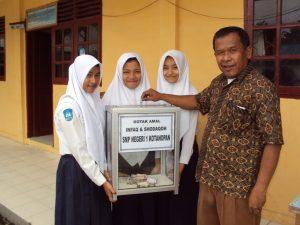 Terlihat dalam gambar, Irsan Hasibuan, S.Pd memperlihatkan kotak amal Infak dan sodaqoh SMP Negeri 1 Kotanopan, dari siswa untuk siswa.